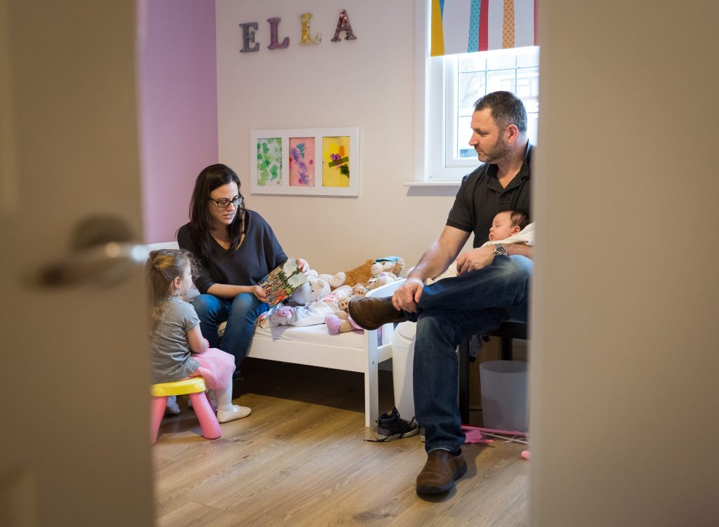 Photos of newborn, older sister and the parents in the older sister's room, mum is reading a book - natural and very cosy scene photographed by family and children photographer based in Enfield, London