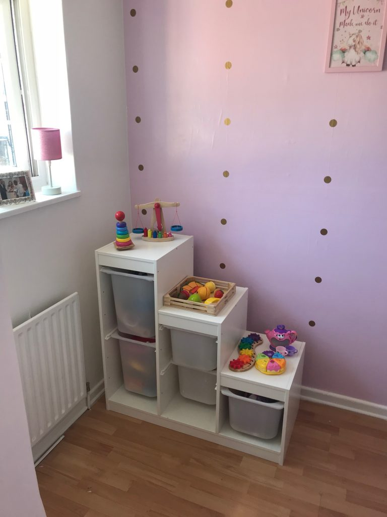pink girls bedroom ikea storage wooden colourful toys unicorn picture on the wall