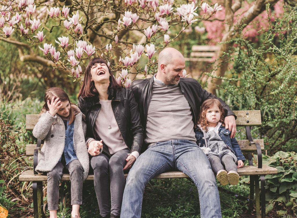 Family of four mum dad sisters siblings sitting in the park Forty Hall Enfield London mum laughing dad is looking at kids and the kids look awkward Photoshoot taken by family Enfield Photographer