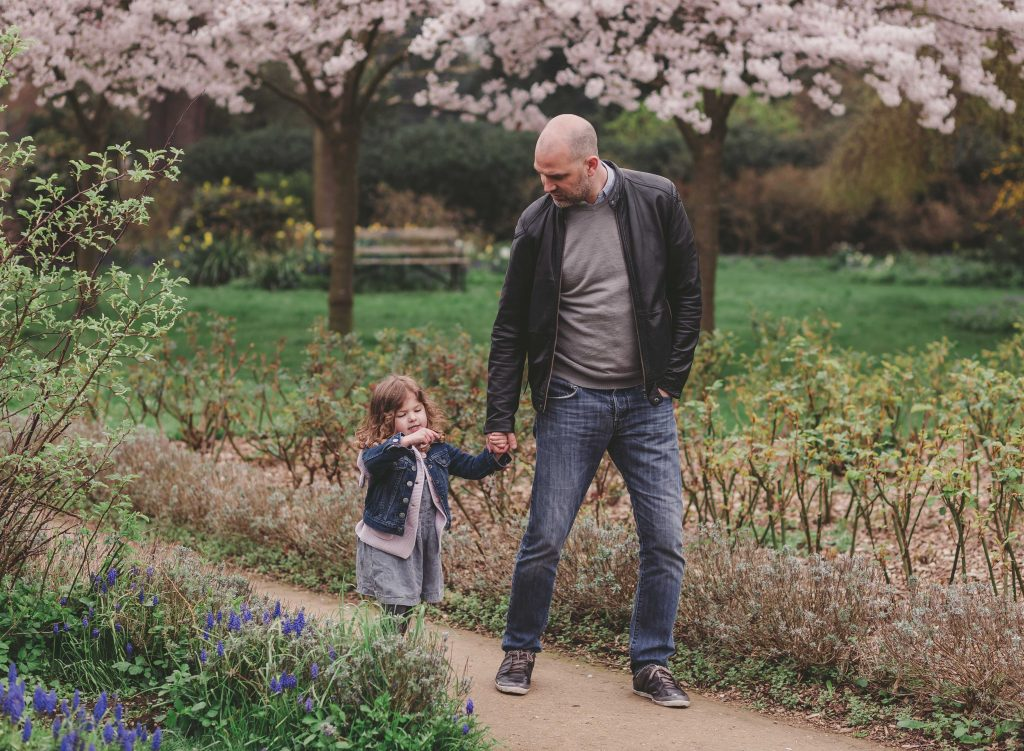 dad and daughter having fun time together holding in Enfield park London photographer
