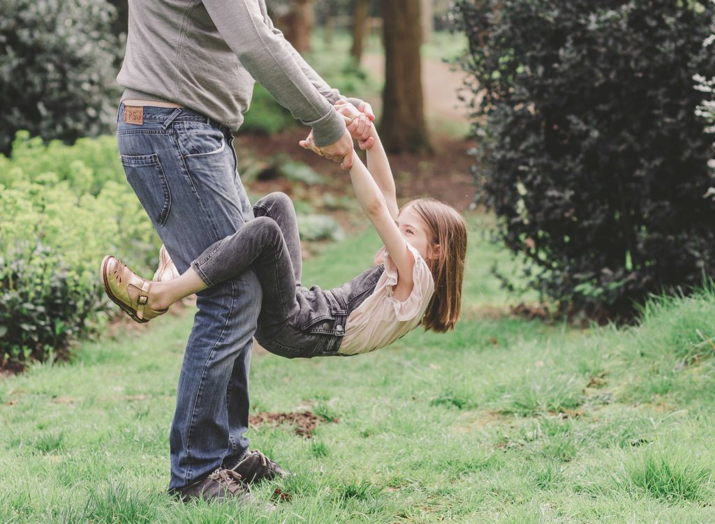 dad and daughter having fun time together holding hands daughter hanging down in Enfield park London photographer