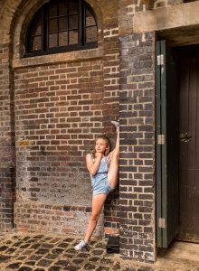 dancing gymnastics standing on one foot near the wall of Camden market of Camden Town London family photographer