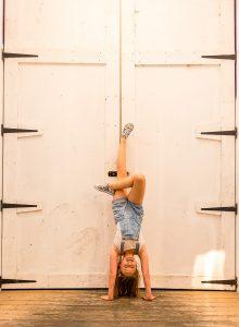dancing gymnastics handstand by the door of Camden market of Camden Town London family photographer